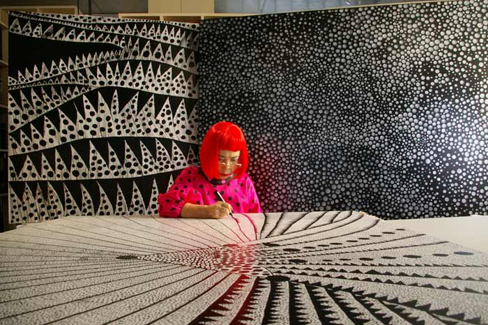 Yayoi Kusama signing an exhibit.